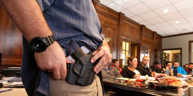 """Damon Thueson shows a holster at a gun concealed carry permit class put on by """"USA Firearms Training"""" in Provo, Utah. (Photo by George Frey/Getty Images)"""