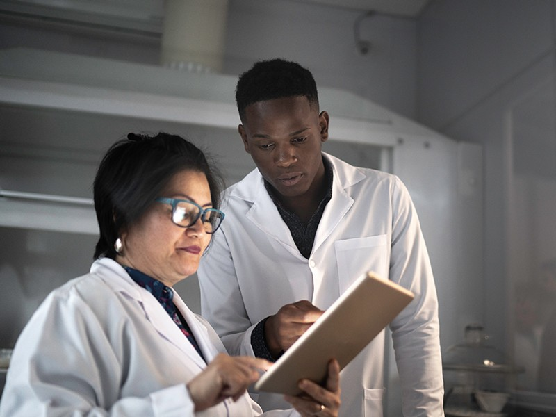 Colleagues analyzing information in a digital tablet while working in a laboratory.