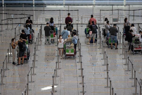 Waiting for shuttle buses to mandatory government-designated quarantine hotels in the arrival hall at the Hong Kong International Airport on Tuesday.