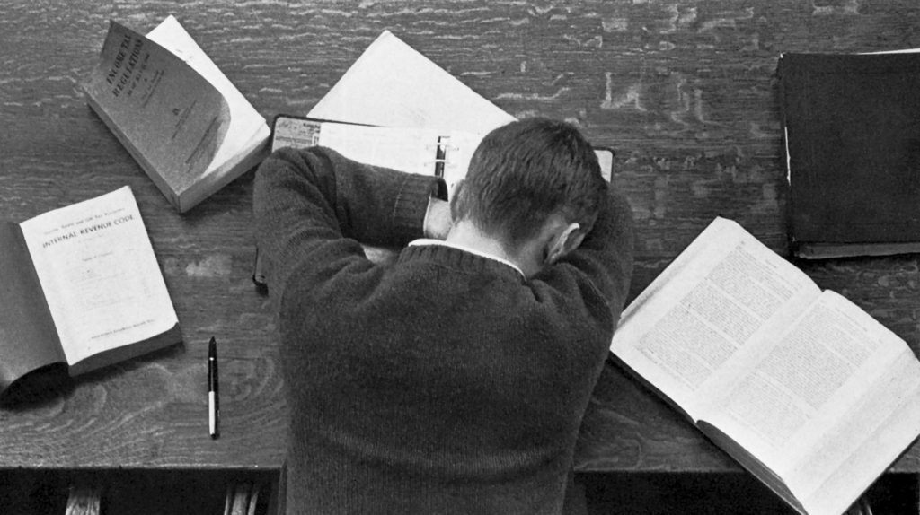 Black and white photo of a student resting his head on book on a table, surrounded by open books.