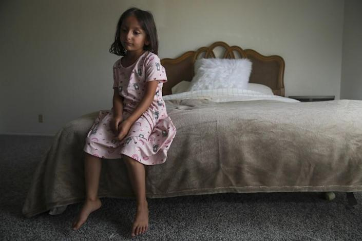 El Cajon, CA - August 23: Afghan refugee child Aqsa Sadat, 6, quietly sits on a bed furnished by the members of Helping El Cajon Refugees group on Facebook on Monday, Aug. 23, 2021 in El Cajon, CA. (Irfan Khan / Los Angeles Times)